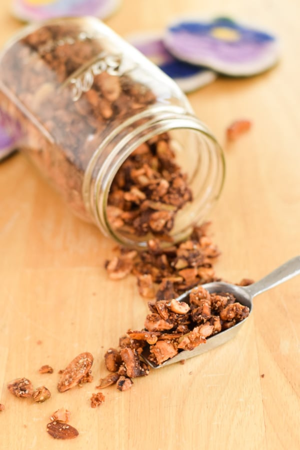 A metal scoop full of granola in front of the Ball jar container, lying on the counter with granola spilling out