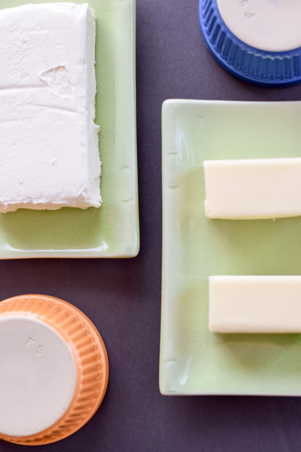 Cream cheese and butter on two small rectangle plaates