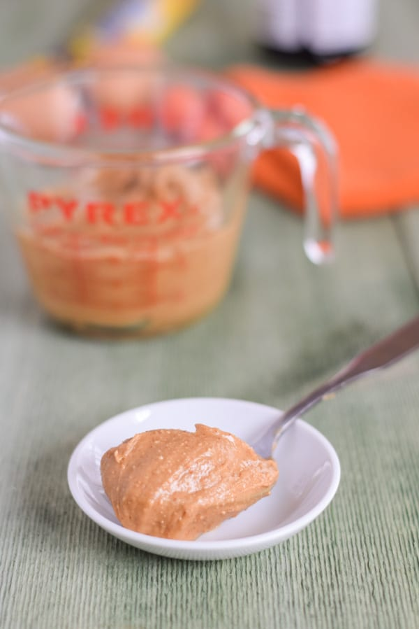Heaping teaspoon of peanut butter on a small dish in front of a Pyrex measuring cup of peanut butter.