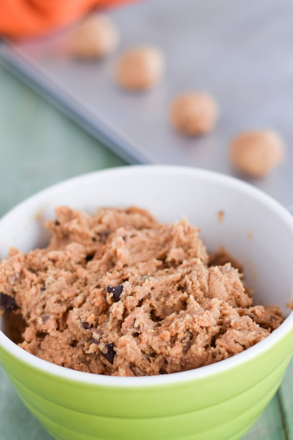 A bowl full of cookie dough with a baking sheet of raw dough balls in the background