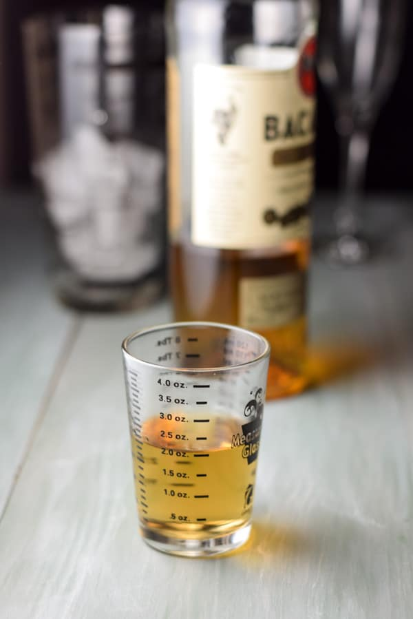 Rum measured out with the bottle and ice filled shaker in the background