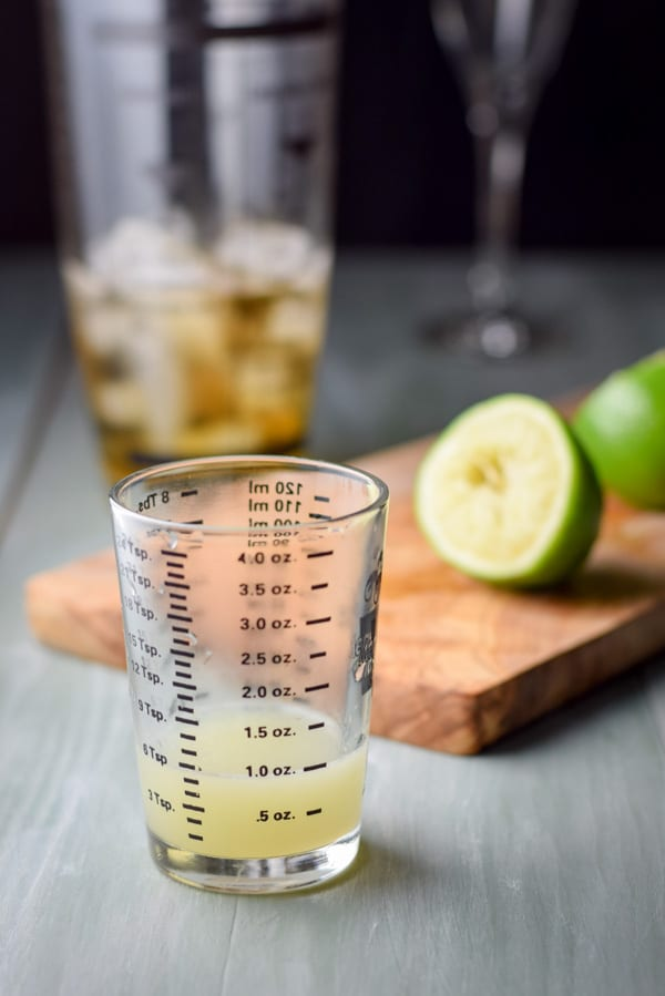 Fresh lime juice in a measuring glass with a board with cut lime and the shaker in the background