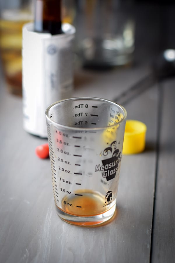 Three dashes of bitters in a glass with the bottle, spoon, shaker and glassware in the background