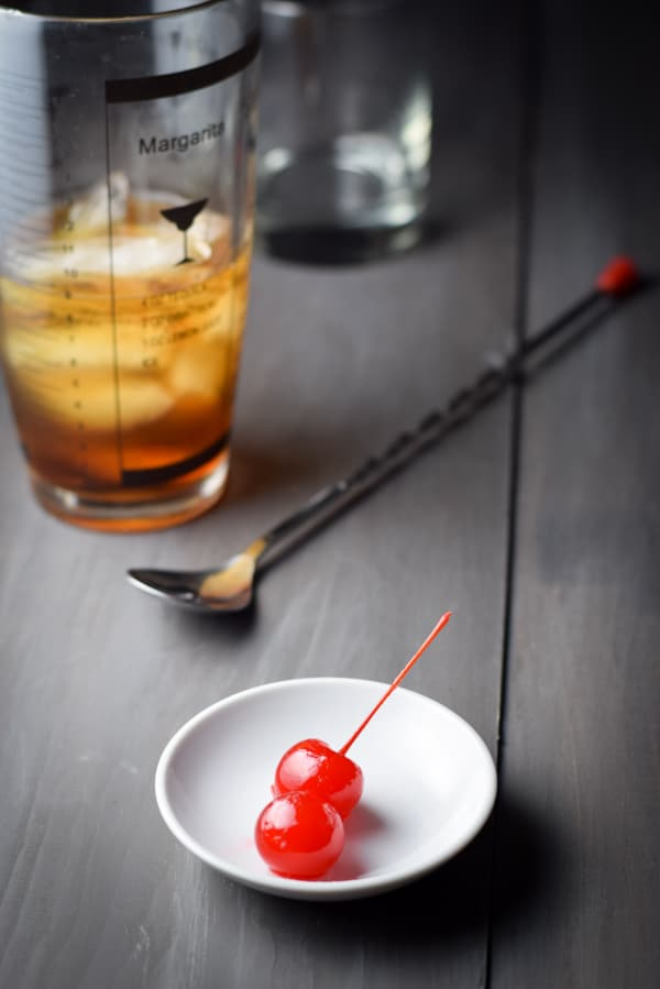 Two cherries on a small white dish with the spoon, shaker and glass in the background