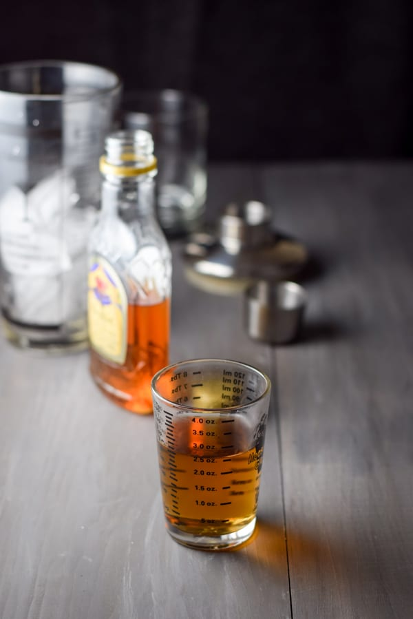 Whiskey measured with the bottle, shaker and glass in the background