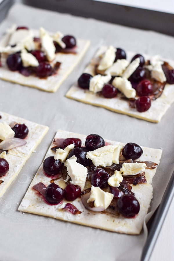 A pan with the puff pastry squares with onion, cherries and chunks of cheese on them