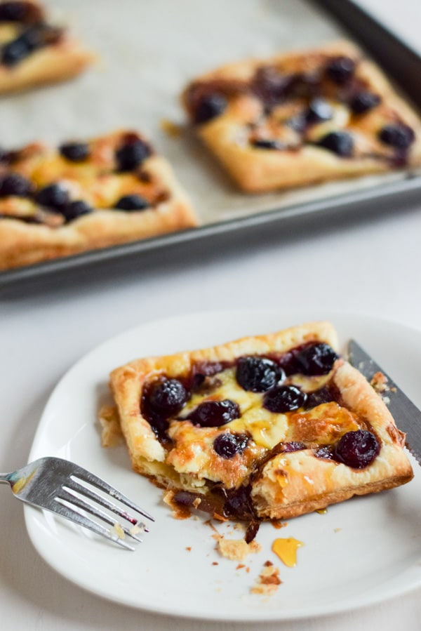 A white plate with flakey puff pastry covered with cherries, onion and cheese in front of the pan of tarts