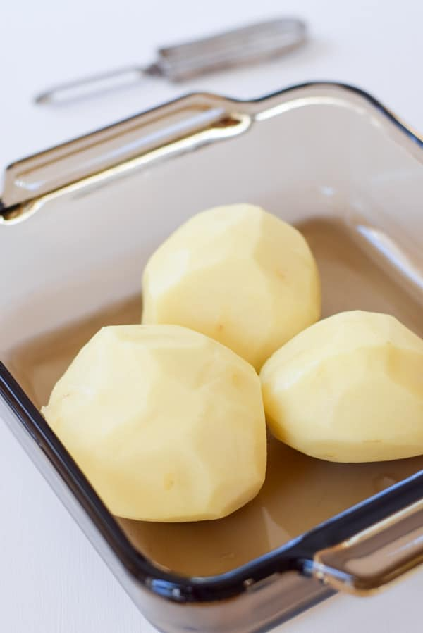 View from above of three washed, peeled whole potatoes sitting in a 9x9 glass casserole dish.