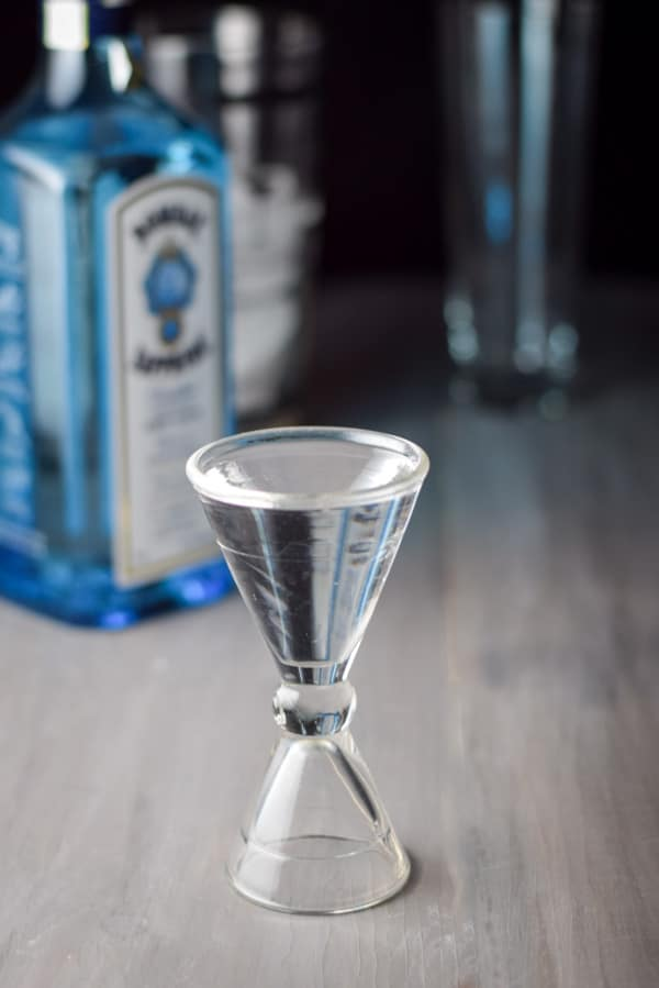 Gin poured out in a glass jigger with the gin bottle in the background
