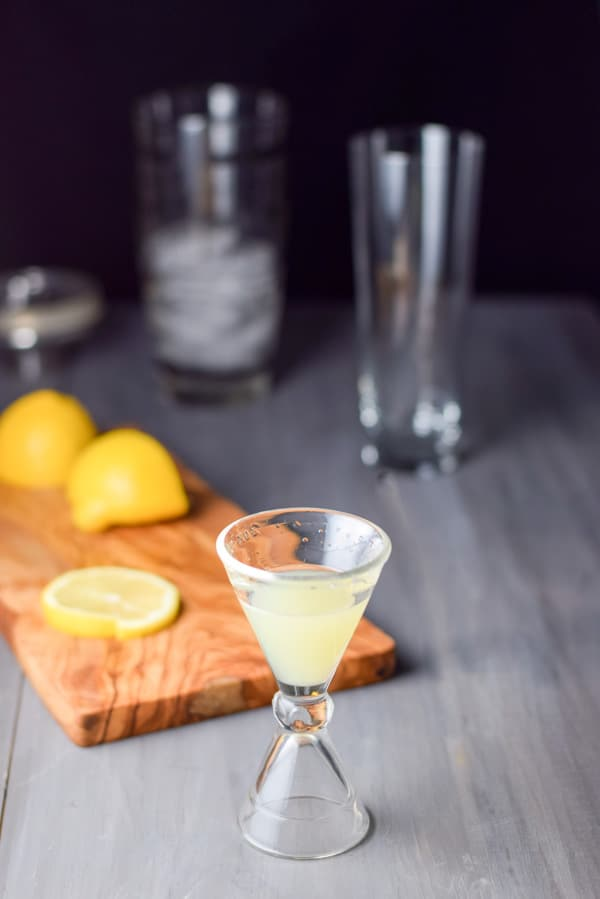 lemon measured out with a wooden board with cut lemons. There is a cocktail shaker and glass in the background