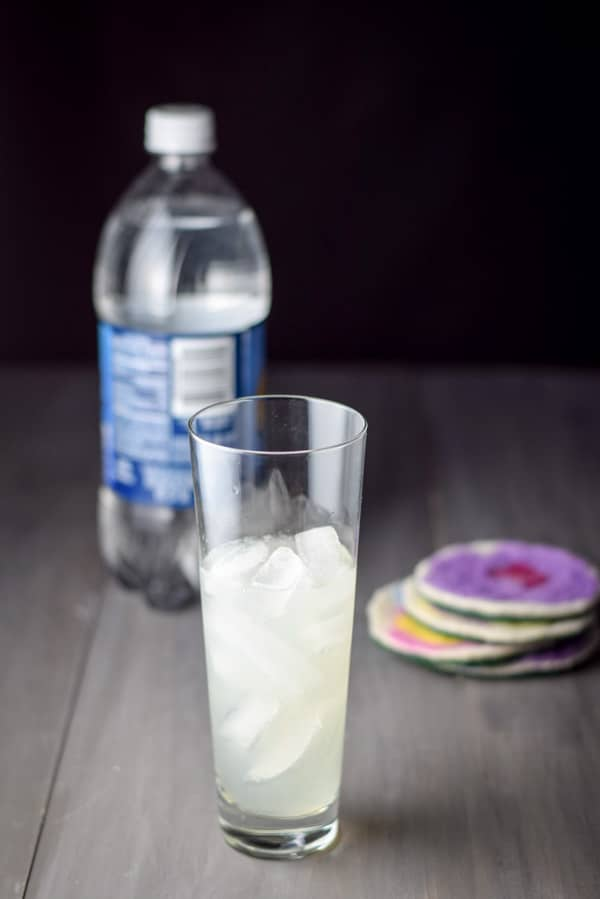 The gin and lemon poured into the glass with club soda in the background