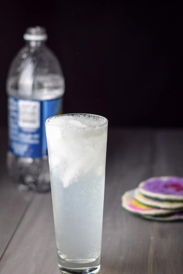Club soda poured into the cocktail with the bottle in the background