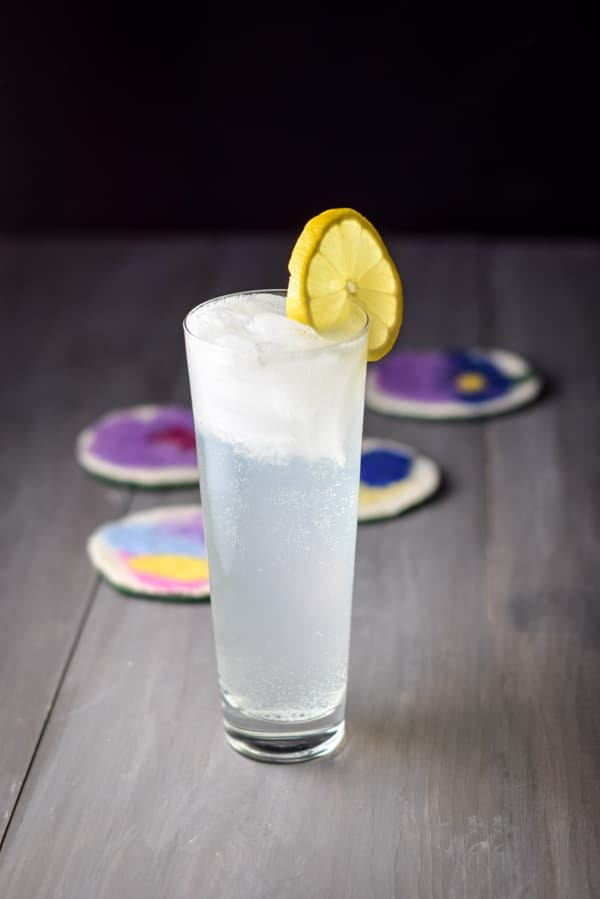 A tall glass of the tom collins cocktail with a lemon wheel on the rim