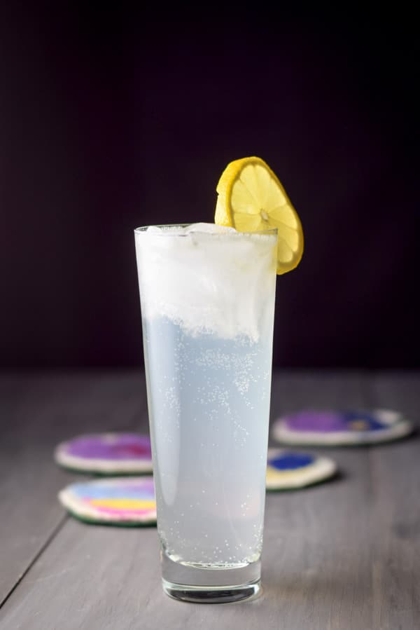 Vertical view of the cloudy cocktail in a flared glass with lemon as the garnish