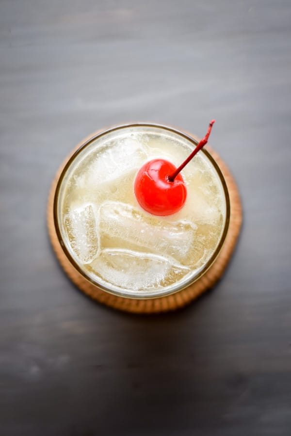 Overhead view of the whiskey sour with a red maraschino cherry floating on top