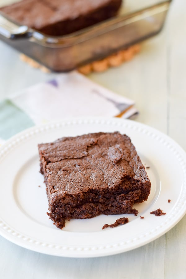 A brownie on a white plate with the square glass pan in the background