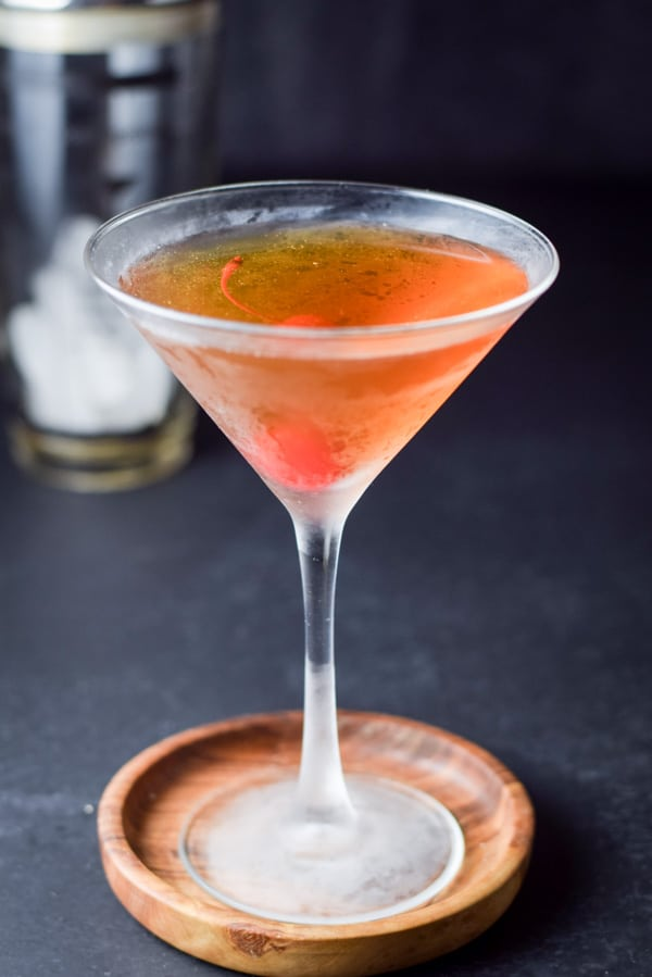 Rob roy in a frosty glass with a maraschino cherry in it