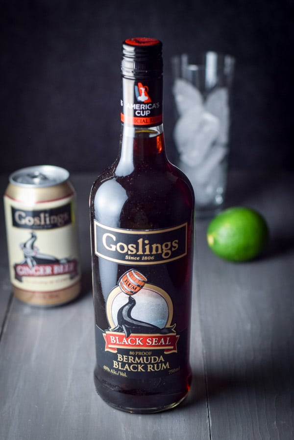 Bottle of Goslings Bermuda black rum with a can of Goslings ginger beer, a lime and a tall glass full of ice in the background.