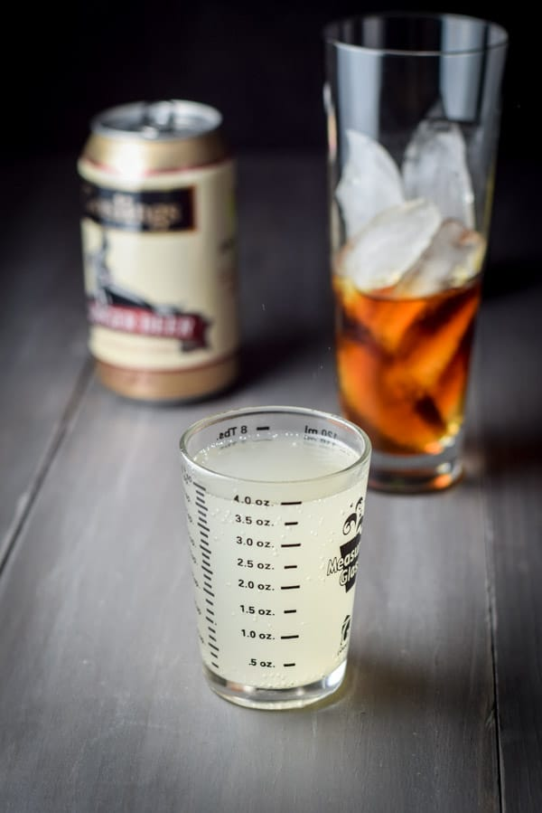 Measuring glass full of ginger beer in the foreground, with the can of ginger beer and the rum poured into the glass of ice standing in the background.