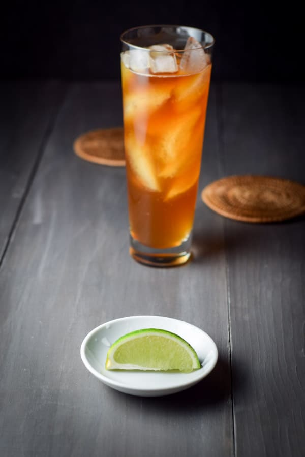 In the foreground, a generous wedge of a lime in a small bowl, with the dark and stormy cocktail in the background.