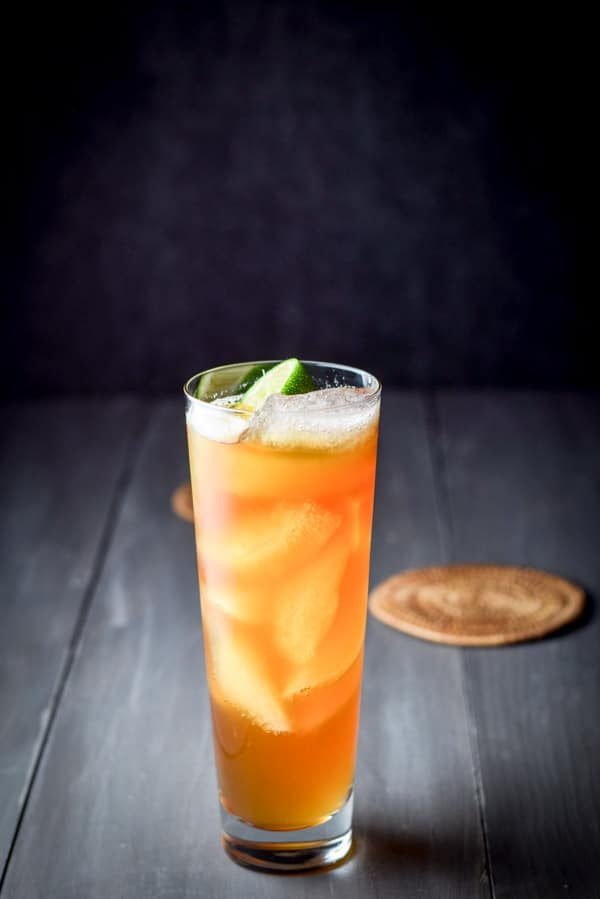 Vertical view of the dark and stormy cocktail with lime wedge garnish.