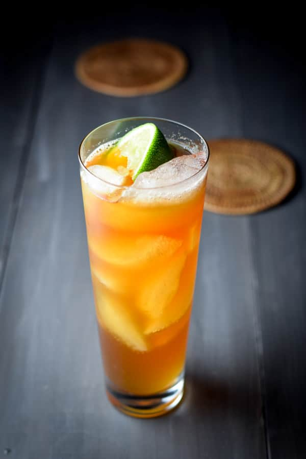 The dark and stormy cocktail in a tall glass with a wedge of lime for garnish.