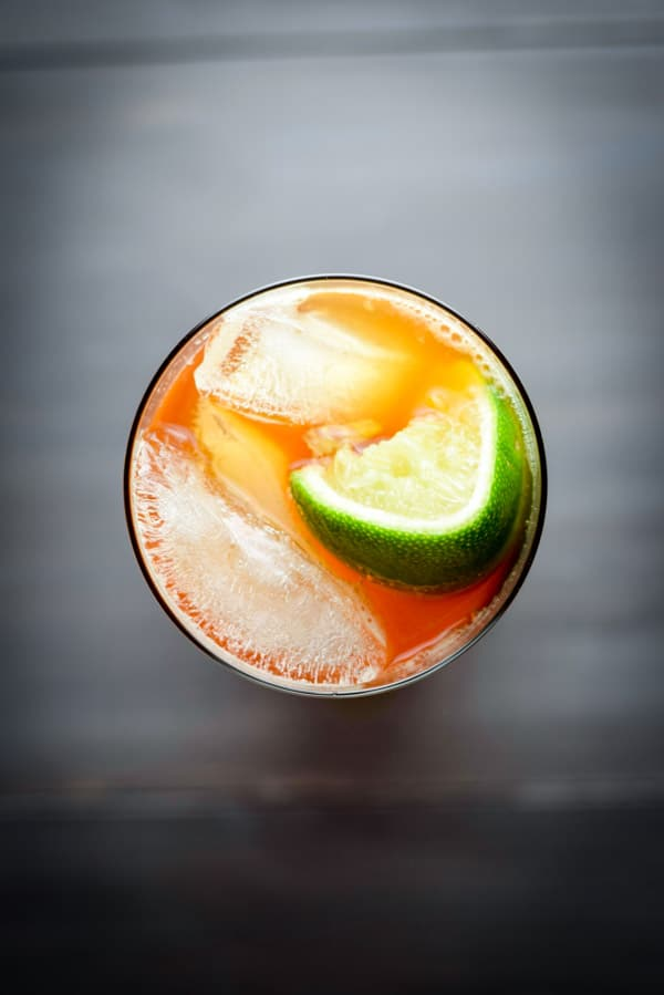 Overhead view of the dark and stormy cocktail with lime wedge garnish and ice cubes floating on top.