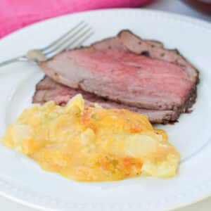 Cheesy potatoes on a white plate with roast beef on it - square