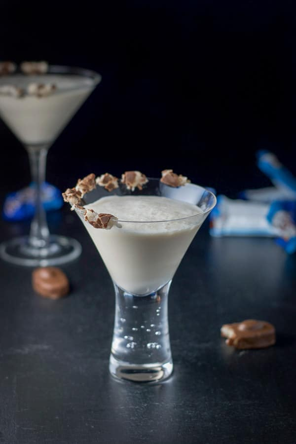 A milk cocktail in a bubble martini glass with the almond joy candy on the rim of the glass. There are candies on the table and wrappers in the background