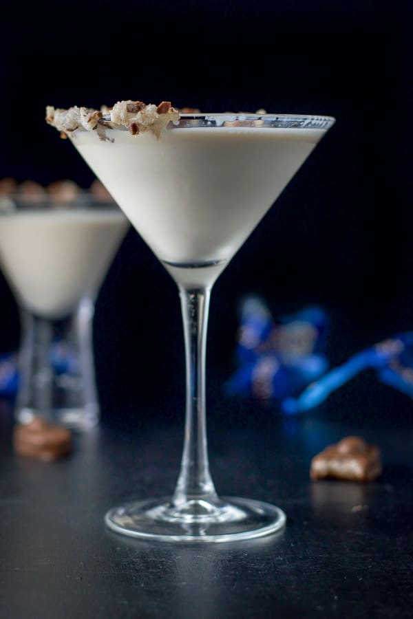 Vertical view of the tall martini glass with the delicious creamy drink in it and smooshed candy bars on the rim