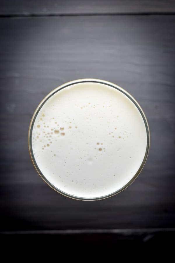 Overhead view of a foamy cocktail on a grey table