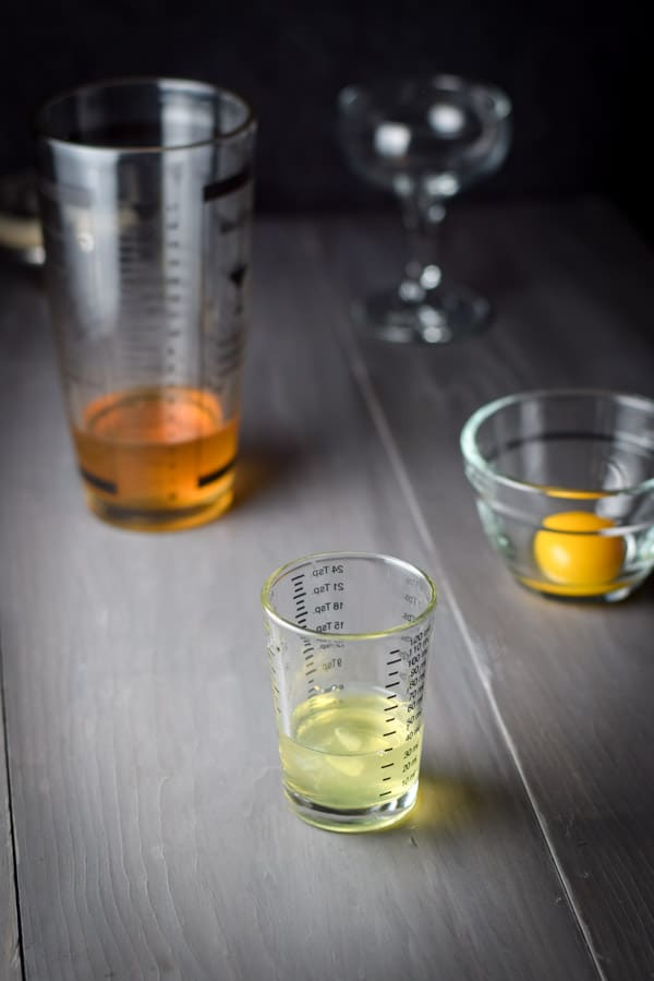 Egg white in a measuring glass with a cocktail shaker and glass in the background