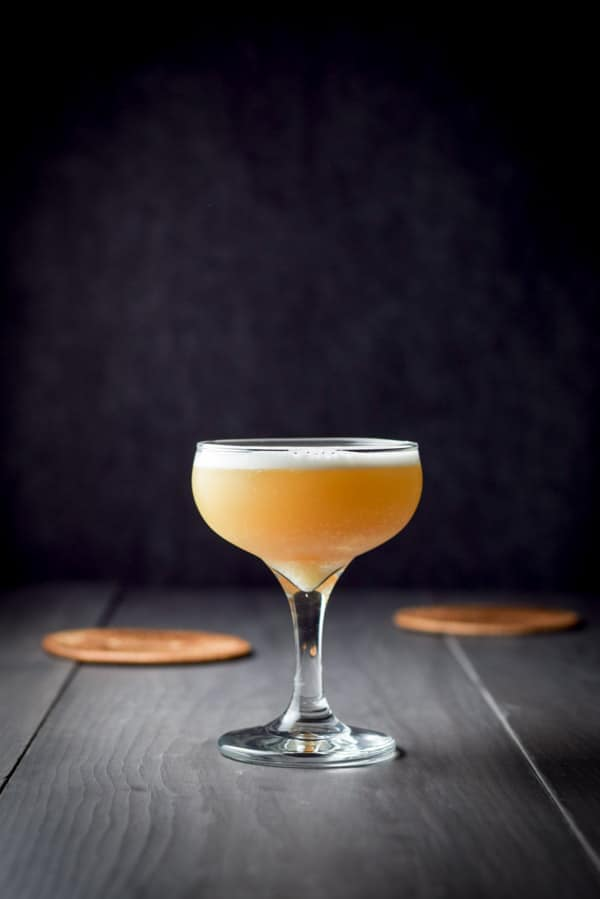The amber cocktail with a foam head in vertical view