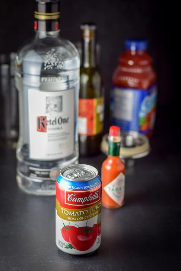 Tomato juice, vodka, clamato juice, olive brine and tabasco on a table