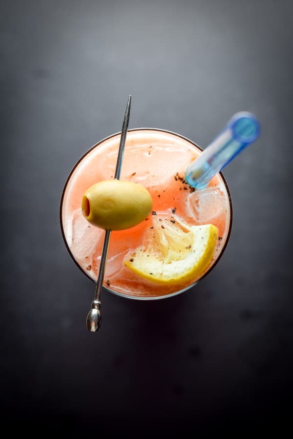 Overhead view of the cocktail garnished with a green olive, lemon and pepper