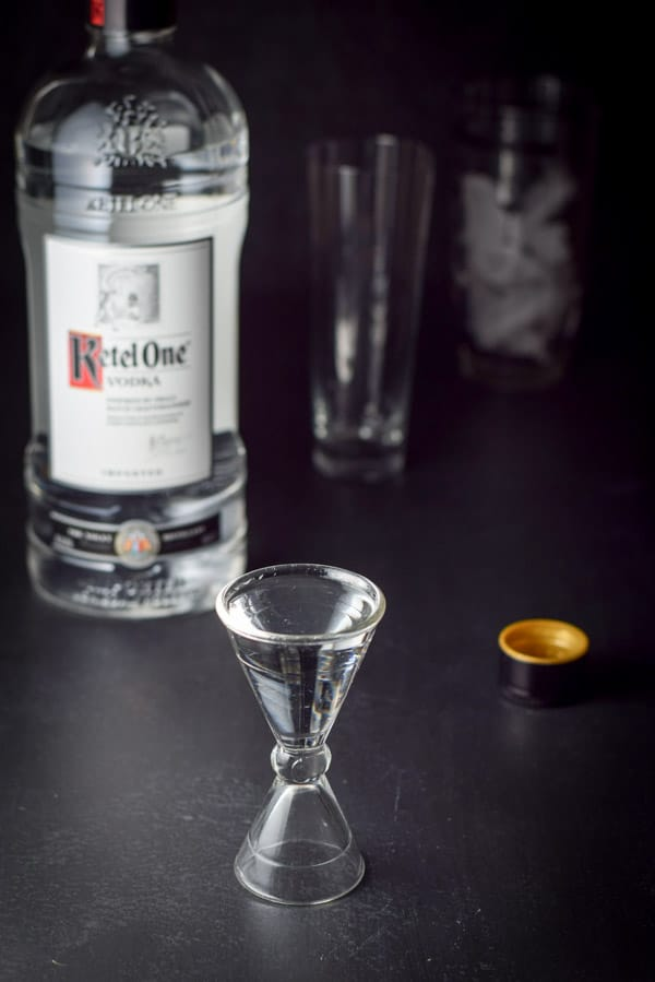 Two ounce shot glass of vodka, with bottle of Ketel One vodka, the empty glass and a cocktail shaker half full of ice in the background.