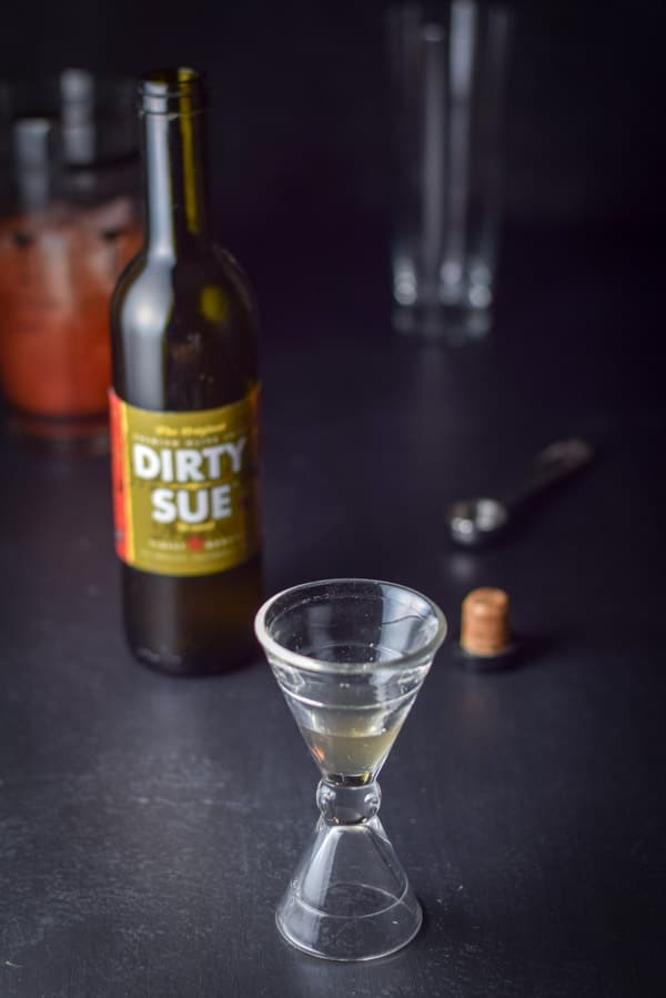 The shot glass half full of olive brine, with the bottle of Dirty Sue olive brine, the cocktail shaker containing the other ingredients and an empty glass in the background.