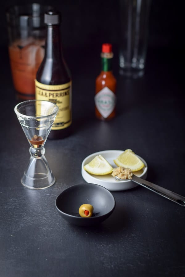 An olive, two lemon wedges, a spoon full of horseradish, spices, a bottle of Worcestershire sauce, a bottle of Tabasco sauce, the cocktail shaker of ingredients and the empty glass.
