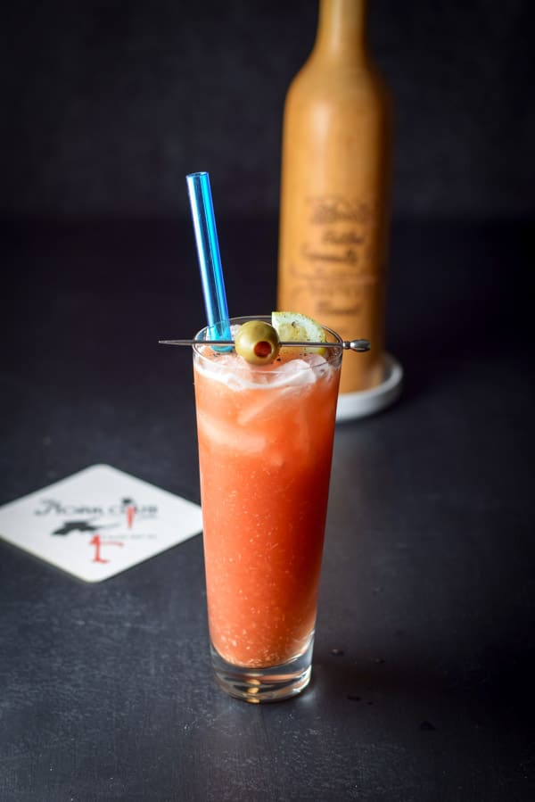 The bloody Mary garnished with the pepper mill in the background