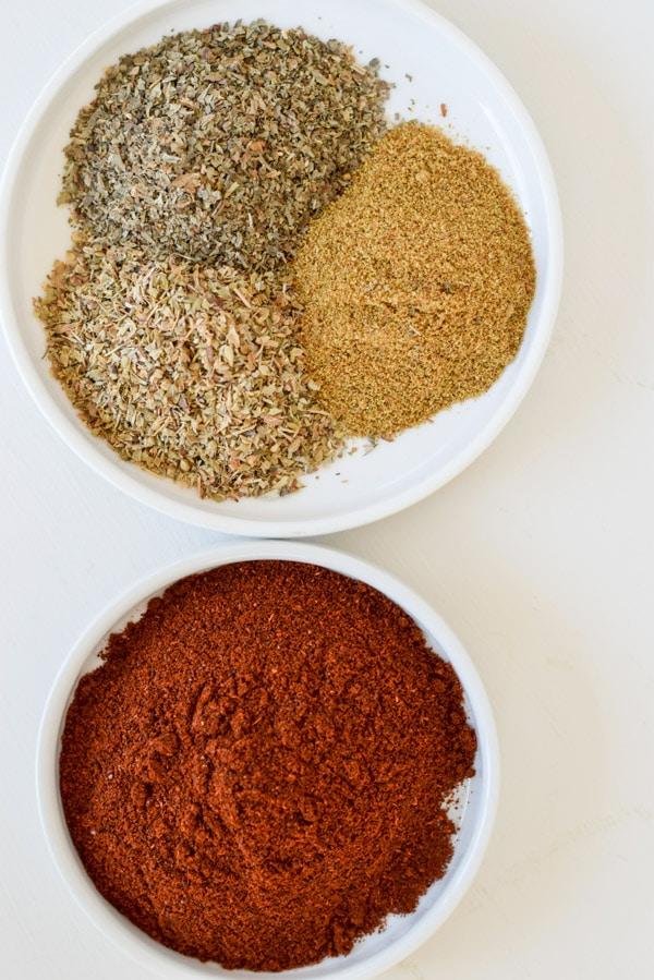 Chili powder, cumin, basil and oregano in small white dishes