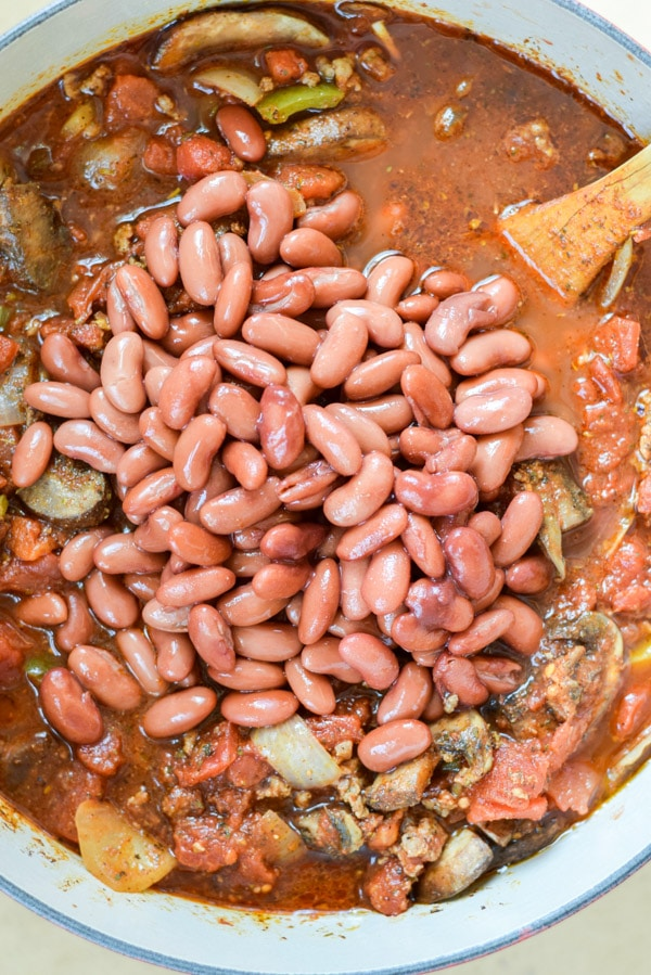Kidney beans added to the chili in a Dutch oven