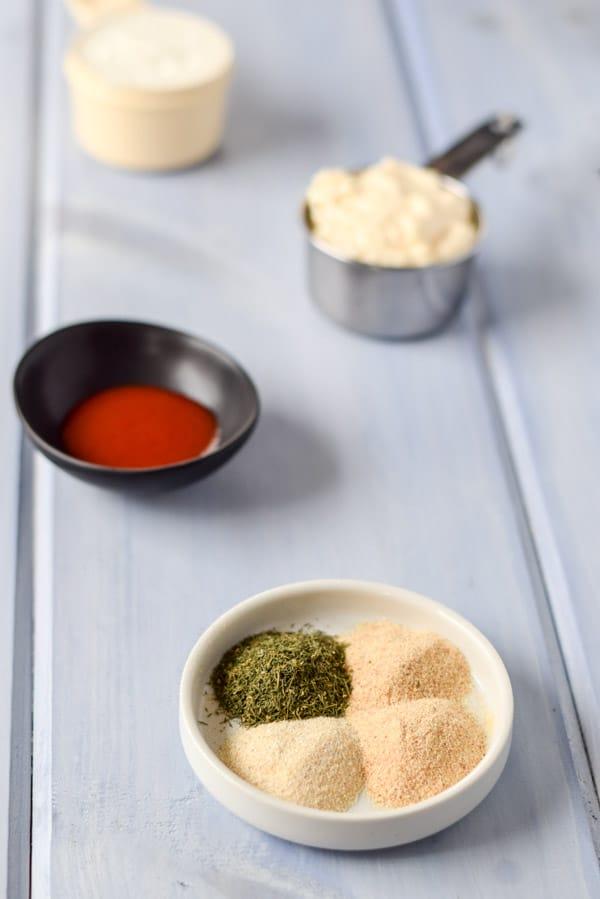 Garlic and onion powder and herbs in a white plate with sriracha sauce, mayo and yogurt