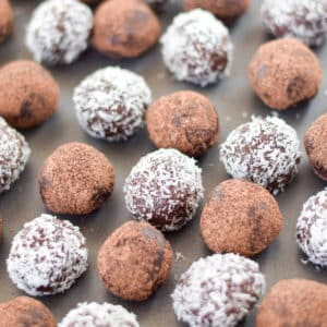 Chocolate rum balls on a pan, some are rolled in coconut and the others in cocoa - square