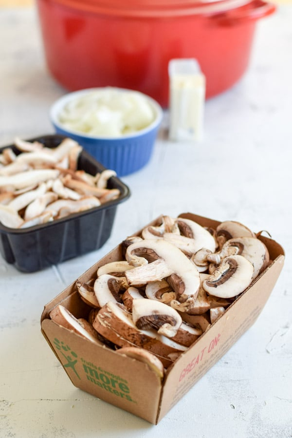 Sliced mushrooms in front of butter, flour and a red pan