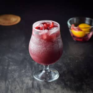fruit added red wine sangria with a small glass bowl of it in the background - square