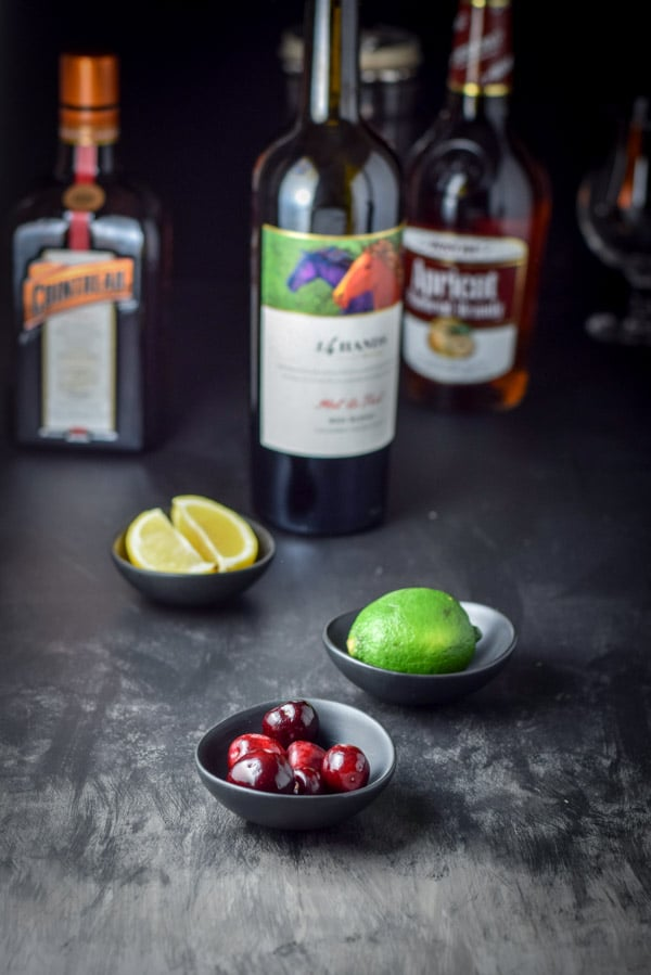 Cherries, lime and lemon in little black bowls with a bottle of wine, apricot brandy and Cointreau in the background
