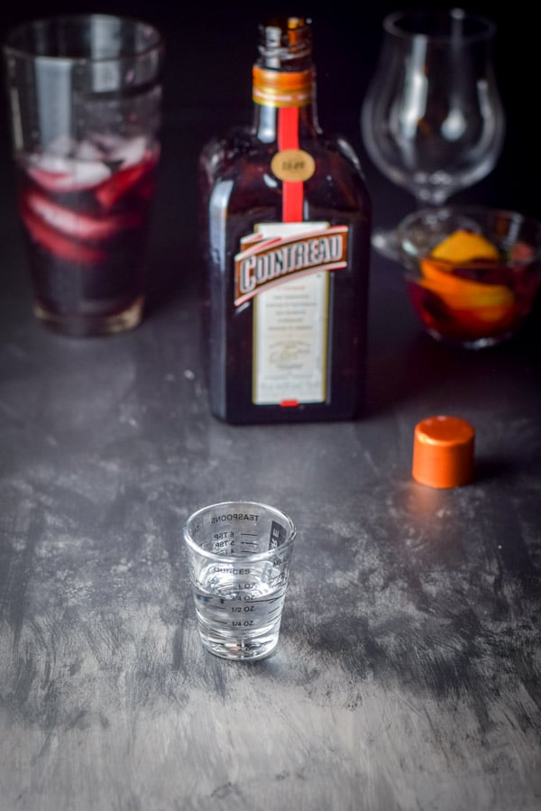 Cointreau measured out with the bottle and the shaker in the background