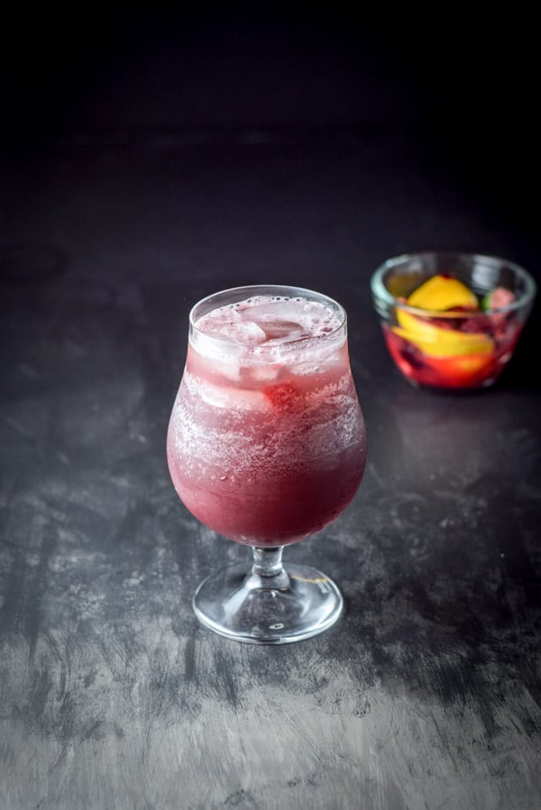 Club soda poured into the tulip glass filled with the sangria
