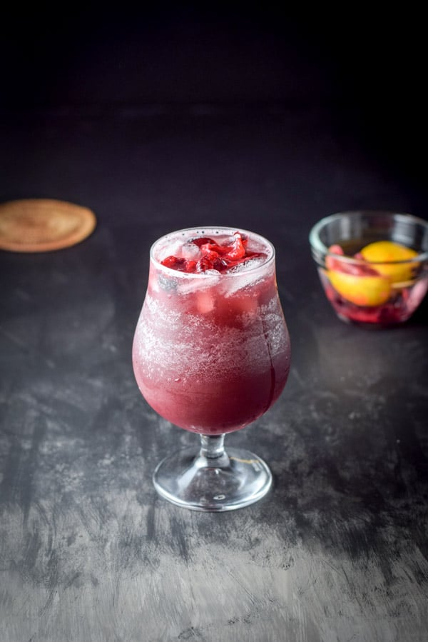 fruit added to the red wine sangria with a small glass bowl of it in the background