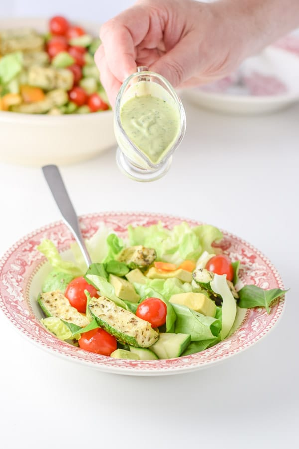 A male hand starting to pour dressing on the salad